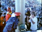 1975 MONTAGE Children watching super-hero characters in costumes performing mock battles on stage at children's entertainment show/ Hawaii Islands, USA Hawaii