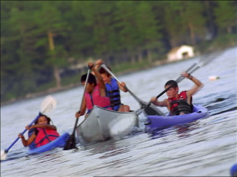 CANTED children wearing life vests rowing canoe + kayaks on lake