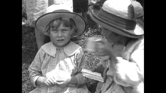 VS children with mugs of milk carrying them and drinking from them at camp for displaced persons of Flood of 1927 / VS men and women vigorously...