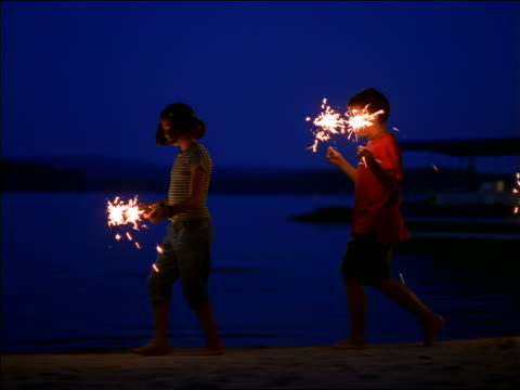 PAN PROFILE children with sparklers walking on lakeshore at dusk