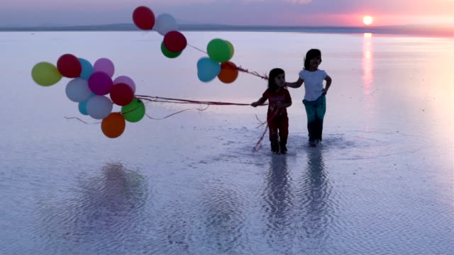 Childrens playing on the water with color balloons  SLOW MOTION