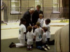 MILLENNIUM 'Children's promise' ITN London Downing St Ext Tony Blair out of No10 with group of children and Sir Richard Greenbury Small child CMS...
