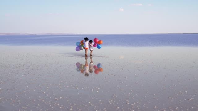 Childrens lopen op het water met kleur ballonnen SLOW MOTION