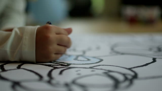 CLOSE UP SELECTIVE FOCUS Child's hand coloring din coloring book