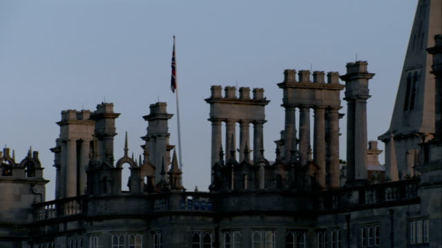 Chimneys and a flag atop Burghley House in Northamptonshire, England. Available in HD.