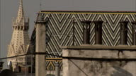 Chimneys stand in front of the patterned roof and steeple of St Stephen's Cathedral in Vienna. Available in HD.