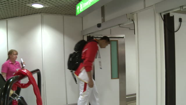 Chinese basketball arrives at Heathrow for 2012 London Olympics / Long walking shots of team with luggage as they walk past airport shops / Yi...