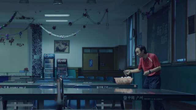 Chinese boy and coach playing ping pong
