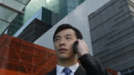 A Chinese businessman answers his cell phone while standing in front of modern office buildings in Singapore.