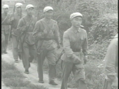 Chinese Communist soldiers Red People's Liberation Army walking w/ rifles at rest along rural road carrying various equipment weaponry