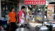 Chinese cook makes noodles at food stall