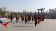 Chinese Dama are dancing waist drum in a park square on a morning According to a report on China's square dancing industry released in 2015 it is...