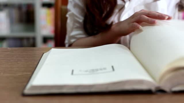 Chinesische weibliche Schüler lesen Buch in Bibliothek, Echtzeit.