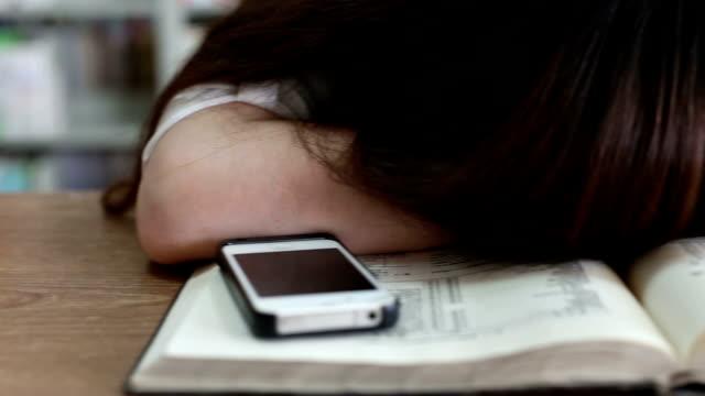 Chinesische weibliche Studentin nehmen nap in Bibliothek, Echtzeit.