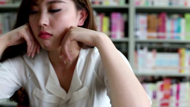 Chinesische weibliche Schüler denken hart in Bibliothek, Echtzeit.