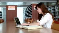 Cinese femmina studente utilizzando il computer portatile in biblioteca, tempo reale.