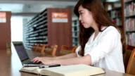 Chinese female student using laptop in library,real time.
