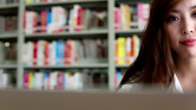 Chinesische Studentin mit laptop in Bibliothek, Echtzeit.