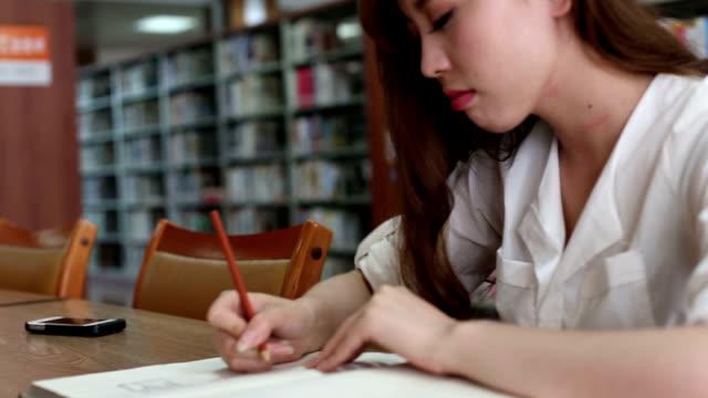 Chinesische weibliche Schüler schreiben auf notebook in Bibliothek, Echtzeit.