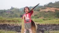 Ein chinesisches Mädchen spielt mit Reis im harvest