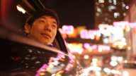 A Chinese man stares in awe through an open car window at the lights of downtown Singapore.
