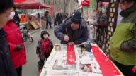 MS Chinese man writing spring festival couplets in street market / xi'an, shaanxi, china