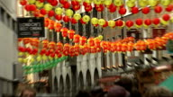 Parade in London Colourful Chinese lanterns strung up across road / people along street with lanterns above