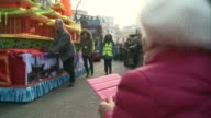 Chinese New Year celebrations in London Woman taking photograph of float in parade Vox pop Chinese Lion performers jumping from pole to pole in...