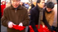 Colourful celebrations in London Chinese men handing out Chinese New Year gifts / Crowds along beneath red lanterns strung across road / Toy red...