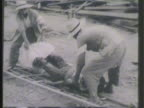 Chinese people lifting dead body onto stretcher others carrying dead body w/ rope bar GRAPHIC carrying burnt body on stretcher World War II WWII...