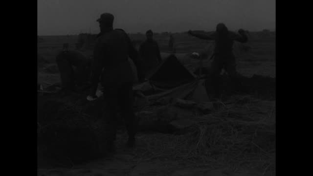 VS Chinese Red Army prisoners wearing quilted winter uniforms stand on plain as UN soldiers guard them with rifles / VS seated prisoners / VS...