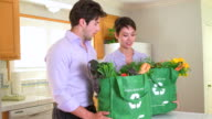 Chinese woman and boyfriend looking through grocery bags
