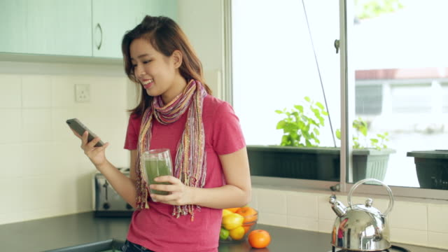 MS Chinese woman in kitchen holding juice whilst using smart phone