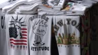 Chinese woman sells tshorts to tourists near Ground Zero / Men hold banner commemorating 911 Man sells American flags to tourists Man shows off his...