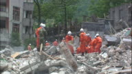 Chinese workers clear piles of earthquake rubble from a school with a bucket brigade