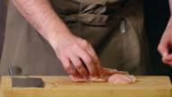 Chopping a chicken fillet.