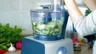 Chopping fresh cucumbers in blender for hash