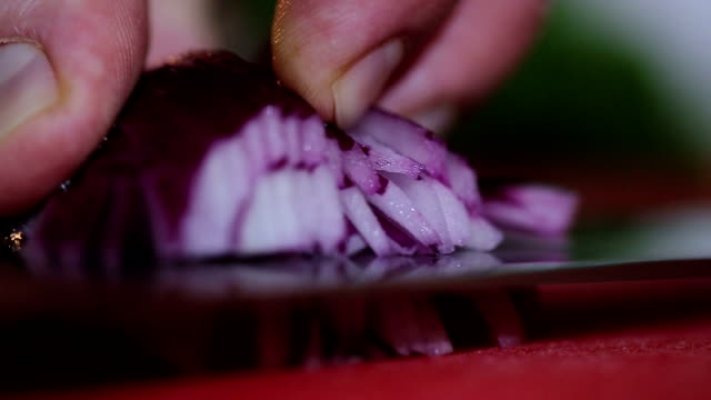 Chopping red onions on board