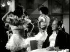 1940 B/W MS Chorus girl leaning back on cabaret table extending legs, man in tuxedo lighting cigarette / New York City, New York, USA