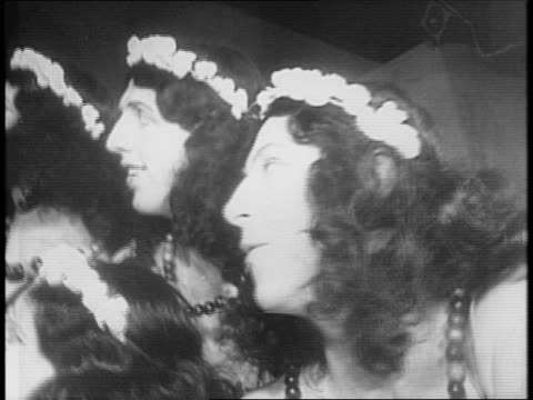 Chorus girls dance on stage / male Columbia University students dressed as women watch from sidelines / men and women dance together in chorus line /...