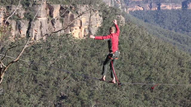 Chris Wallace of Australia walks on a highline rigged between cliffs at Corroboree Walls in Mount Victoria on March 6 2015 in the Blue Mountains...