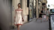 Chriselle Lim wears sunglasses a white and red lace dress and white heels outside the Valentino show during Paris Fashion Week Haute Couture...