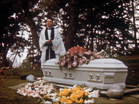 1955 Christian minister speaking behind coffin at funeral service / USA