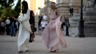 Christina Pitanguy wears a white lace dress Erica Pelosini wears a bandanna a pink lowneck lace dress a pink bag outside the Giambattista Valli show...