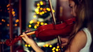 Christmas. Cute little girl playing the violin with Christmas lights behind.