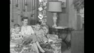 VS Christmas decorations behind them Patricia wife of Captain Harry F Hedlund and two sons Larry Tom sit on sofa for reaction shots / she gets up to...