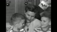 Christmas decorations behind them wife of Captain Harry F Hedlund Patricia and two sons Larry Tom snuggle on sofa and talk about Hedlund she says...