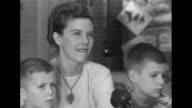Christmas decorations behind them wife of Captain Harry F Hedlund Patricia and two sons Larry Tom sit on sofa for interview / SOT she says she found...