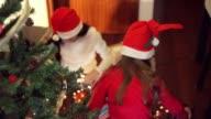 Christmas. Girls un Christmas lights beside the Christmas tree