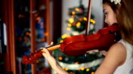 Christmas. Happy girl playing the violin, smiling, with Christmas lights behind.